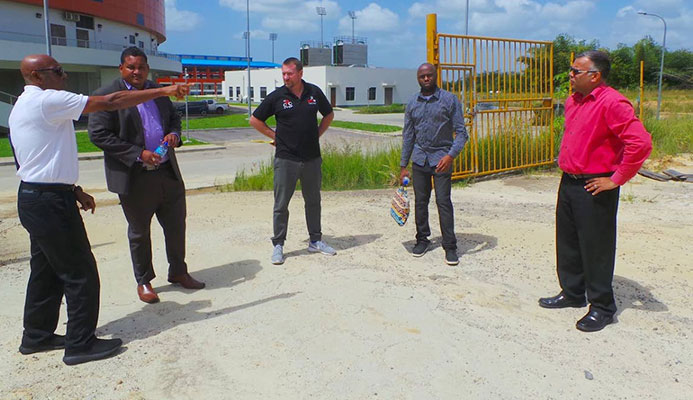 Anthony Creed points to a location on site behind the National Cycling Velodrome as Minister Smith, second from left, Erin Hartwell, centre, Trevlon Hall, second from right, and Jason Williams look on.