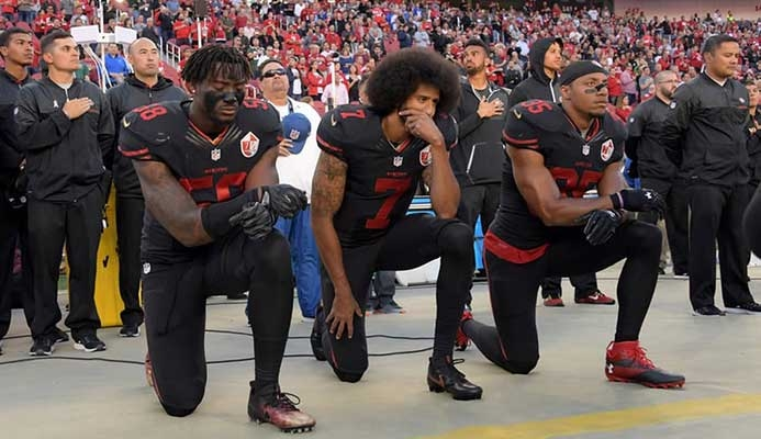 Colin Kaepernick, center, protests before a game against the Arizona Cardinals last October. Photograph: USA Today Sports