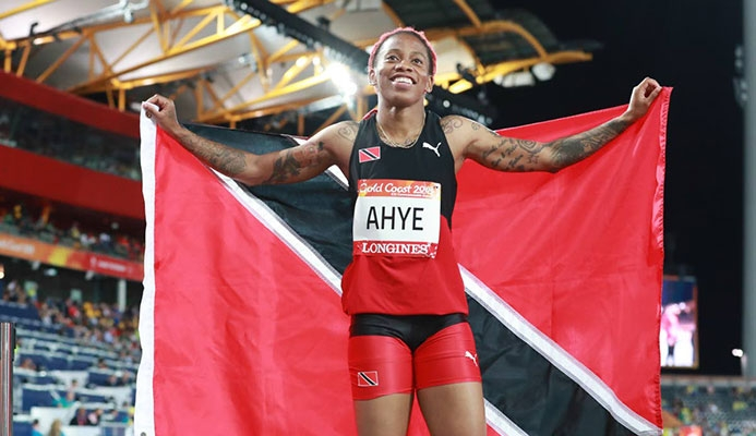 Michelle-Lee Ahye displays the national flag after winning the 100m gold at the Commonwealth Games at Carrara Stadium, Gold Coast, Australia, recently.