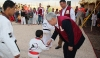 World Taekwondo Federation President Chungwon Choue is handshaking with a child in Zaatari refugee camp in Jordan during the opening ceremony of WTF Taekwondo Academy.