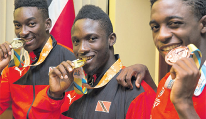 Commonwealth youth 100m sprint prince Adell Colthrust,centre, flanked by fellow countrymen Tyriq Horsford,right, and swimmer Jerron Thompson, following their arrival at the Piarco International Airport on Tuesday night. PHOTO: CA-IMAGES/ALLAN CRANE