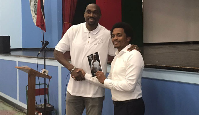 Former pro basketballer Kibwe Trim shows off his book at his alma mater St Mary's College yesterday.
