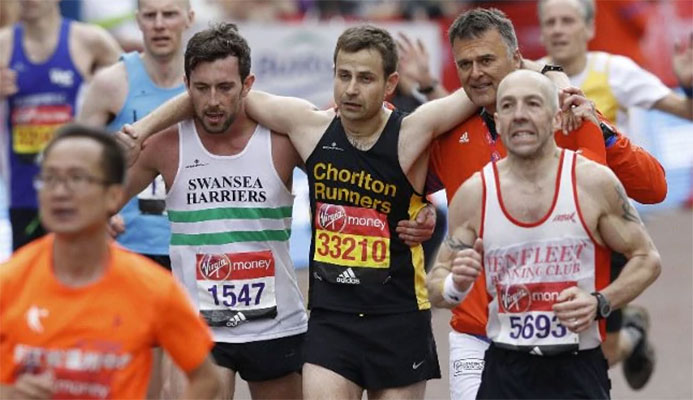 Matthew Rees helps the exhausted runner across the line CREDIT: LONDON MARATHON