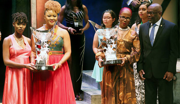 First Citizens Sports Award Winners: Men's champ Jereem Richards, represented by his sister Brittney (left) holds his trophy along with acting Minister of Sport and Youth Affairs Dr Nyan Gadsby-Dolly (second from right) while Michelle-Lee Ahye, represented by her mother Raquel (second from right) holds her trophy, while chairman of the First Citizens Sports Foundation Dr Keith Clifford (right) looks on. Photo: Azlan Mohammed