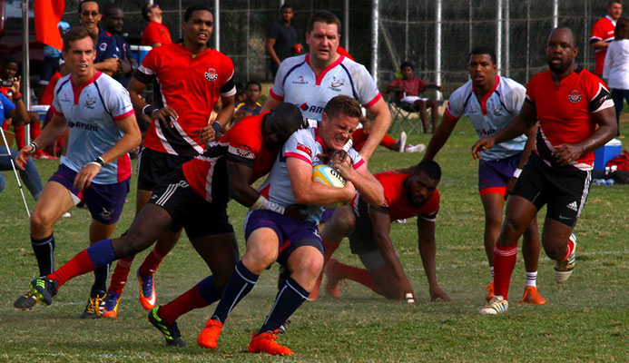 Bermuda's Conor McGowen, centre, is tackled by TT's Jason Quashie in their RAN 15s Tournament clash recently at St Anthony's Ground, Westmoorings.