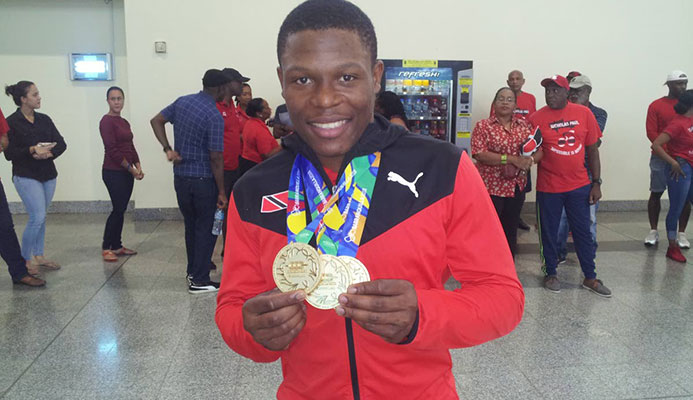 GOLD GALORE: TT cyclist Nicholas Paul shows off his three CAC Games gold medals on his return at the Piarco International Airport yesterday from Colombia.