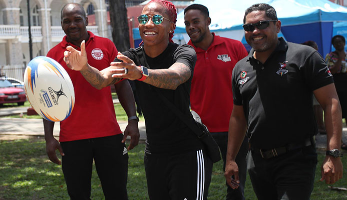 Commonwealth Games 100 metres gold mnedallist T&T's Michelle-Lee Ahye, centre, tries her hand at rugby during the T&T Olympic Committee's observance of International Olympic Day at Woodford Square, Port-of-Spain, back in June.  CA-images/ Allan Crane