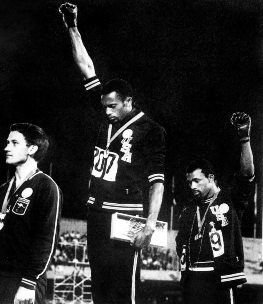 In this October 16, 1968 file photo, US athletes Tommie Smith (C) and John Carlos (R) raise their gloved fists in the Black Power salute to express their opposition to racism in the USA during the US national anthem, after receiving their medal for first and third place in the men's 200m event at the Mexico Olympic Games. At left is Peter Norman of Australia who took second place. AFP PHOTO - -