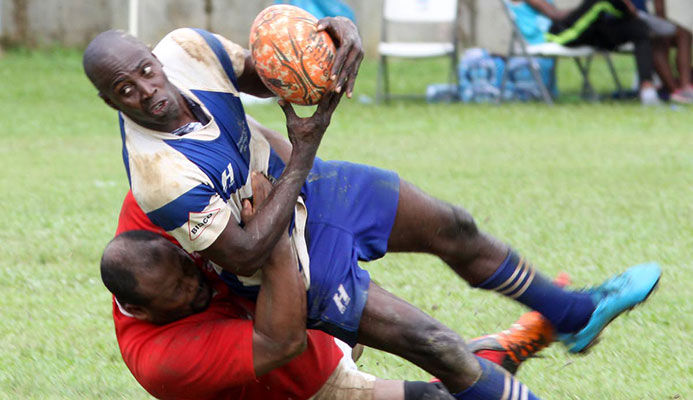 A UWI Tobago player (left) inflicts a crunching tackle on his Northern opponent at a match yesterday in the Police Sevens Rugby Tournament.